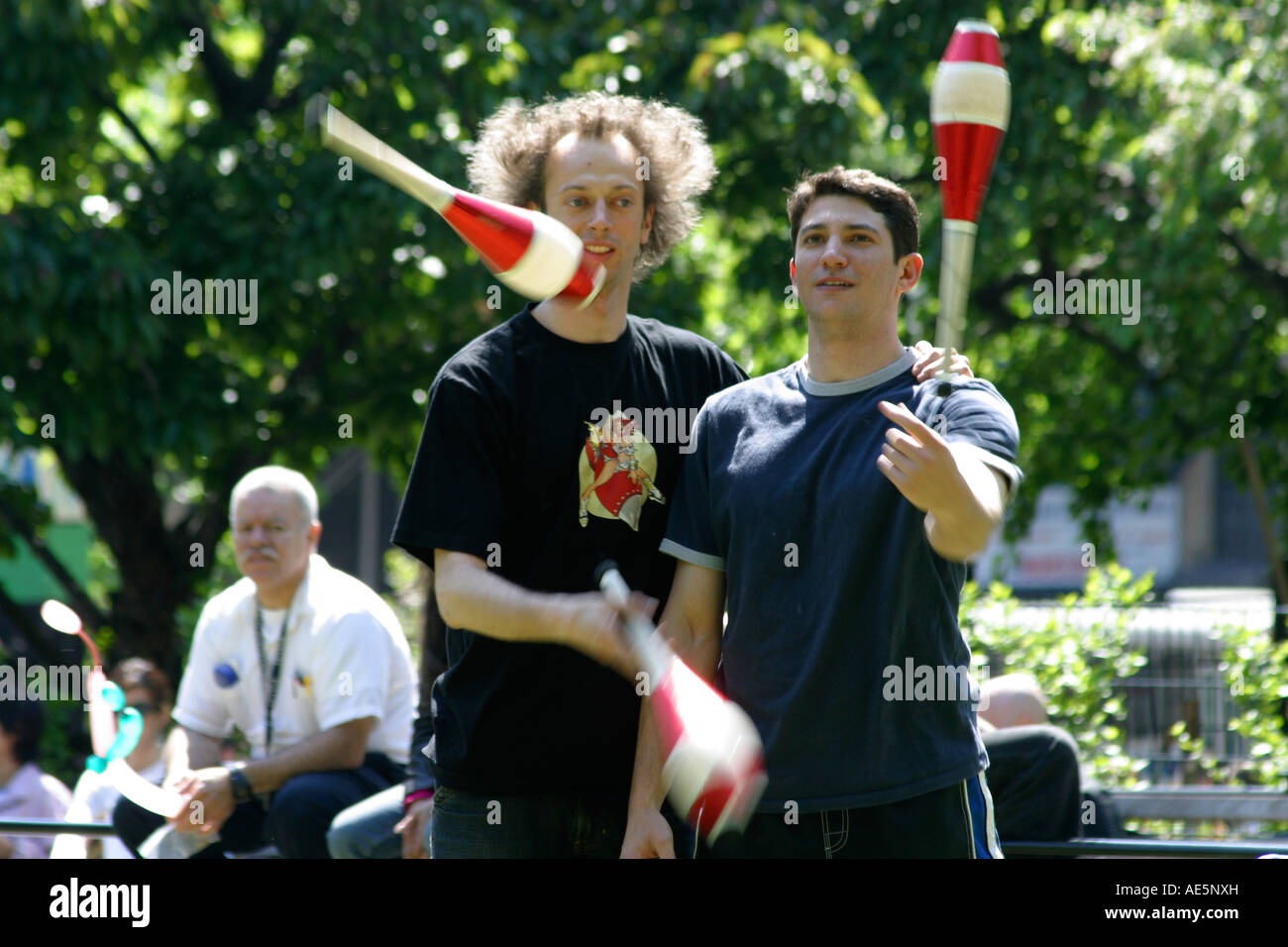 Two men collaborating to jointly juggle three red juggling pins as a spectator observes - Stock Image