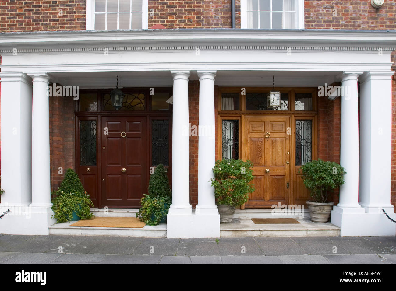 Two Affluent Residential Front Entrances With Wood Doors Columns And Potted  Plants In South Kensington London England
