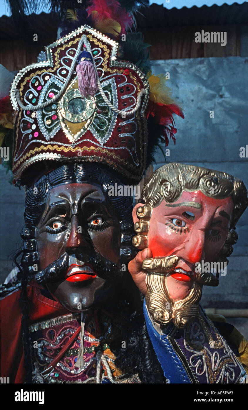 Guatemalan traditional dance performer in a dance mask Dance of the Moors and holding a mask representing a Spaniard - Stock Image