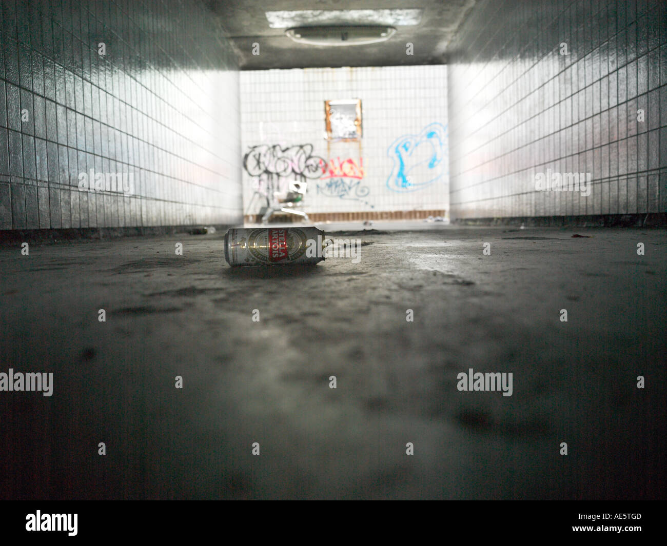 Shopping trolly used by homeless person on a Manchester underpass with graffitti on wall - Stock Image