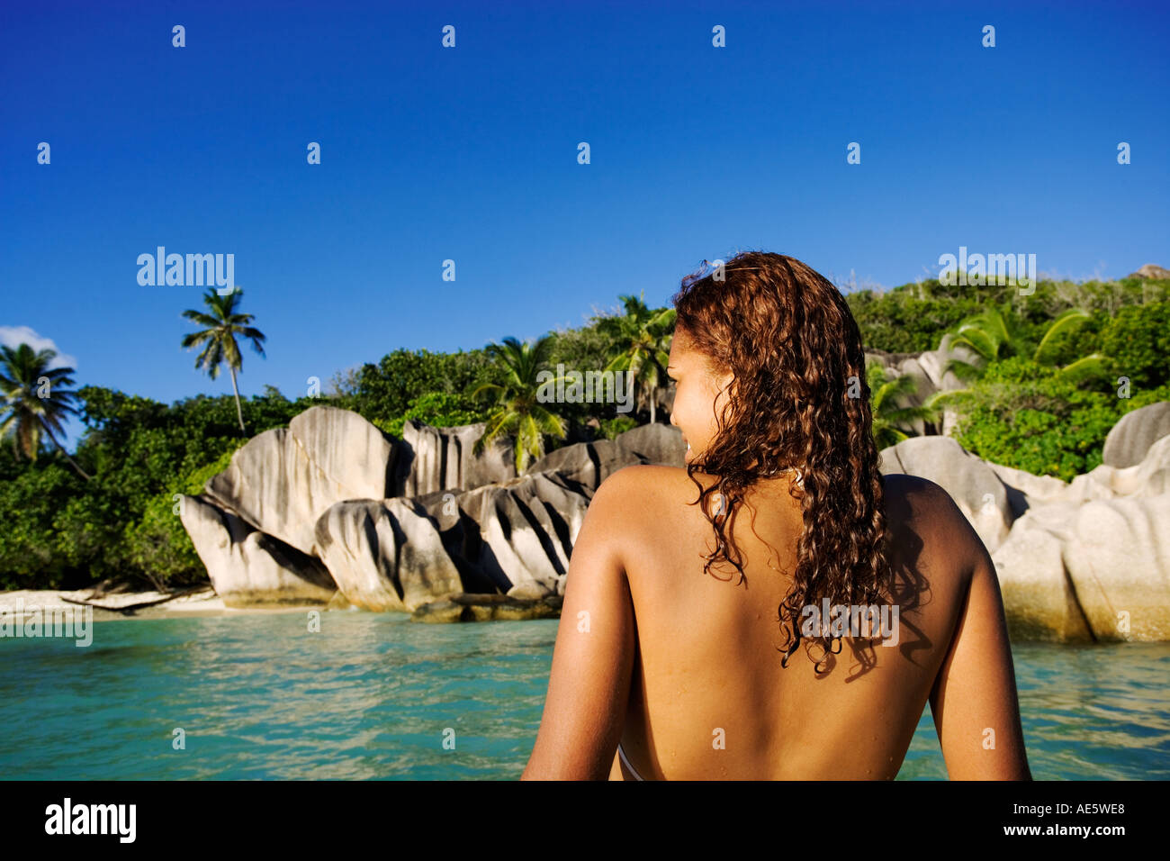 Woman relaxing on boat Granite boulders in the background Anse Source d Argent beach La Digue Island Seychelles - Stock Image