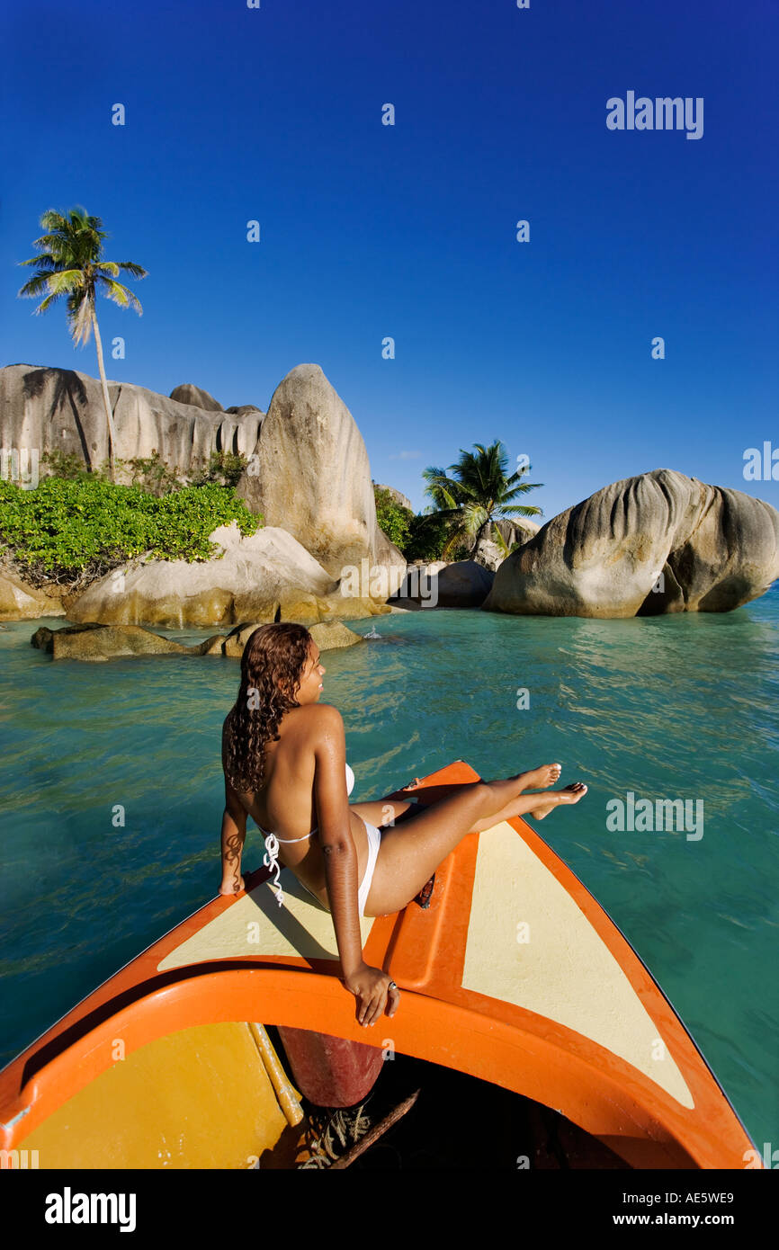 Woman relaxing on boat with granite boulders in background Anse Source d Argent beach La Digue Island Seychelles Stock Photo