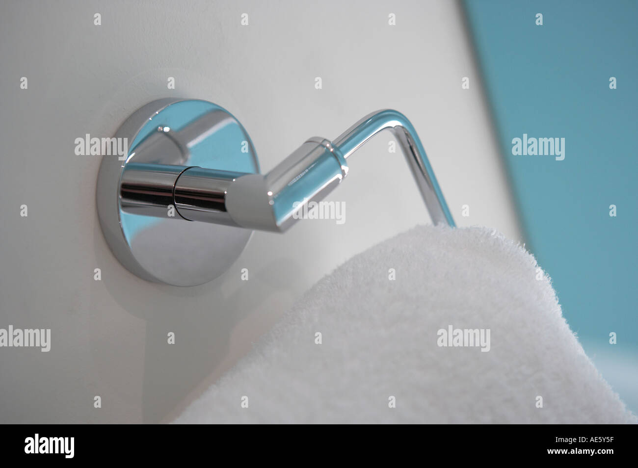 WHITE TOWEL HANGING ON CHROME RAIL IN BATHROOM - Stock Image