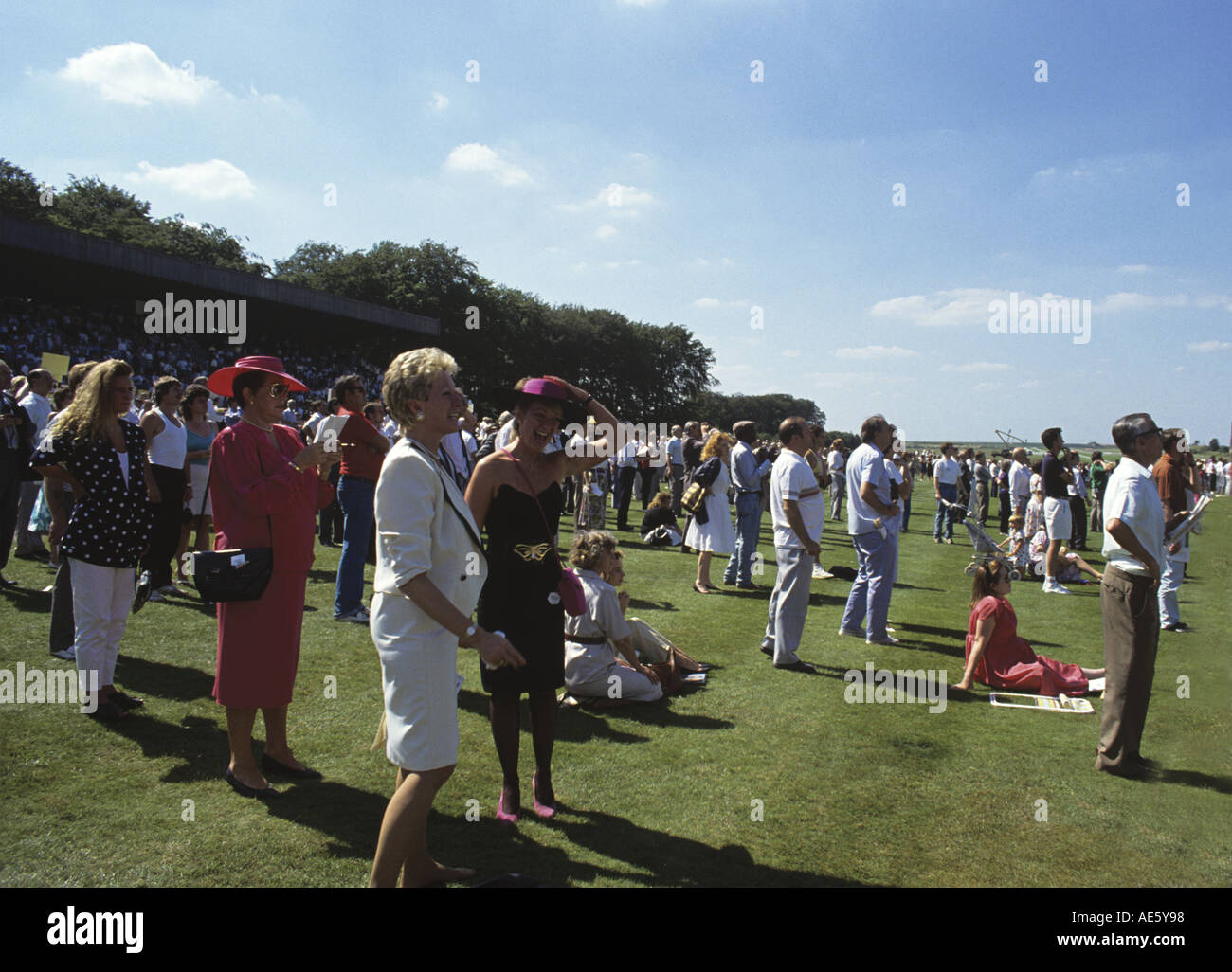 Ladies in summer frocks watching a race at the special summer course at Newmarket Suffolk - Stock Image