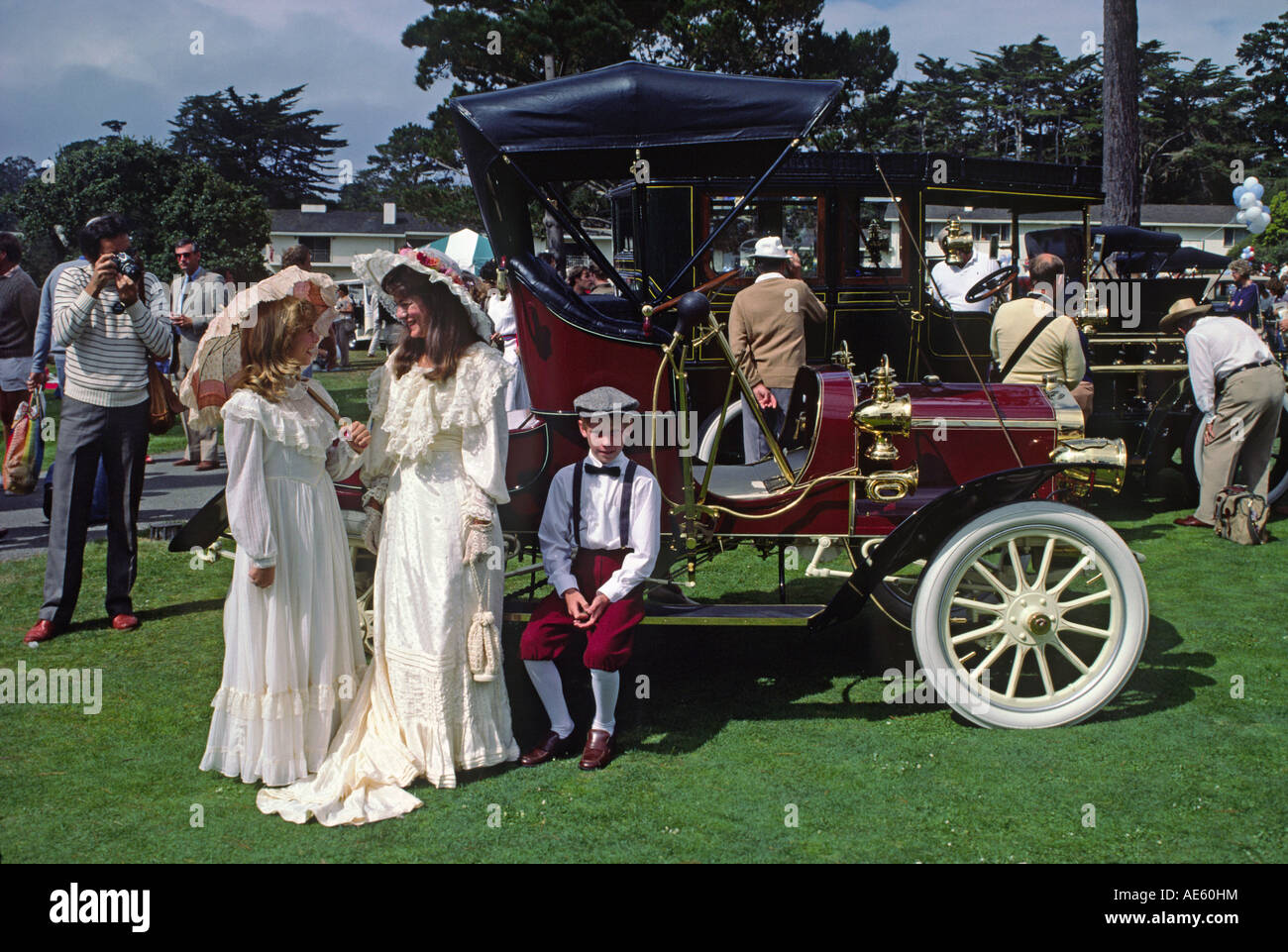 Attendees in period dress next to their 1900 PACKARD at the CONCOURSE D ELEGANCE PEBBLE BEACH CALIFORNIA - Stock Image
