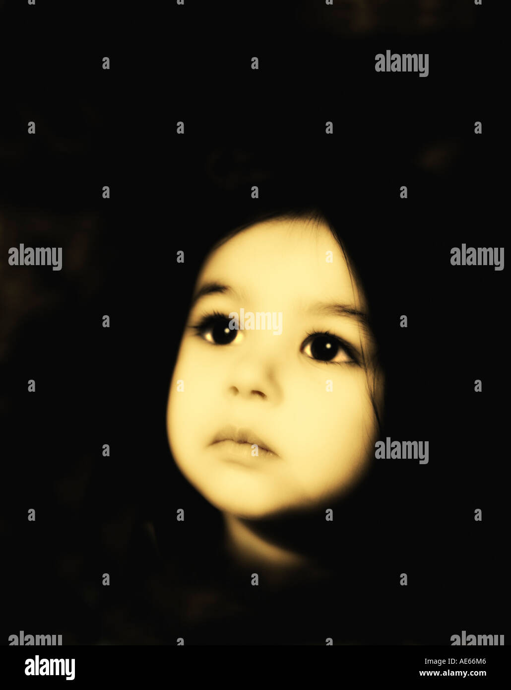 Beautiful enigmatic solitary young girl aged two years looks up with large eyes in hope. Sepia toned Stock Photo