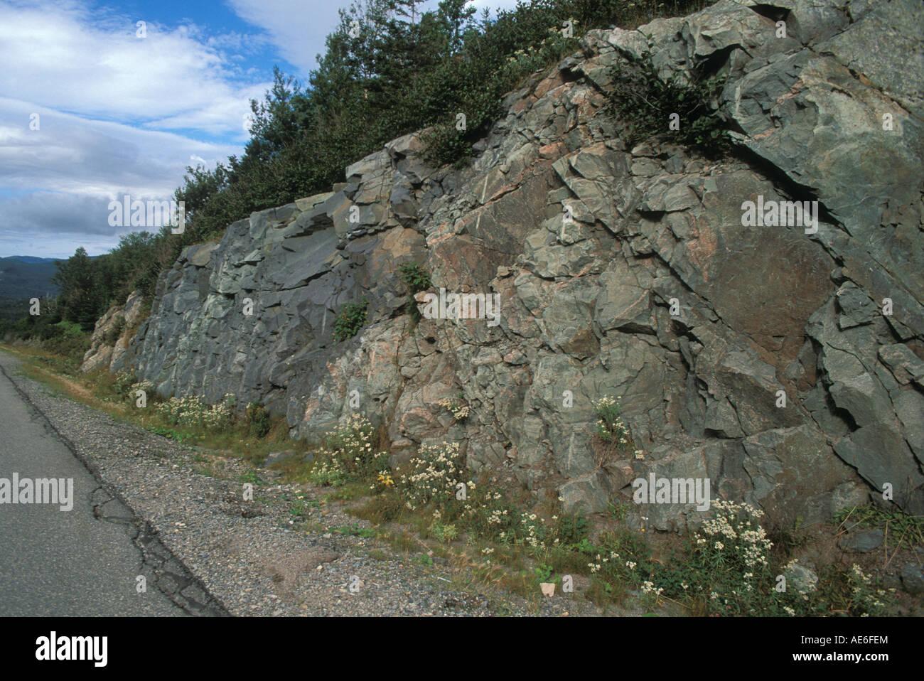 Road cut exposes uniformity layer of rocks Gros Morne National Park Newfoundland Canada - Stock Image