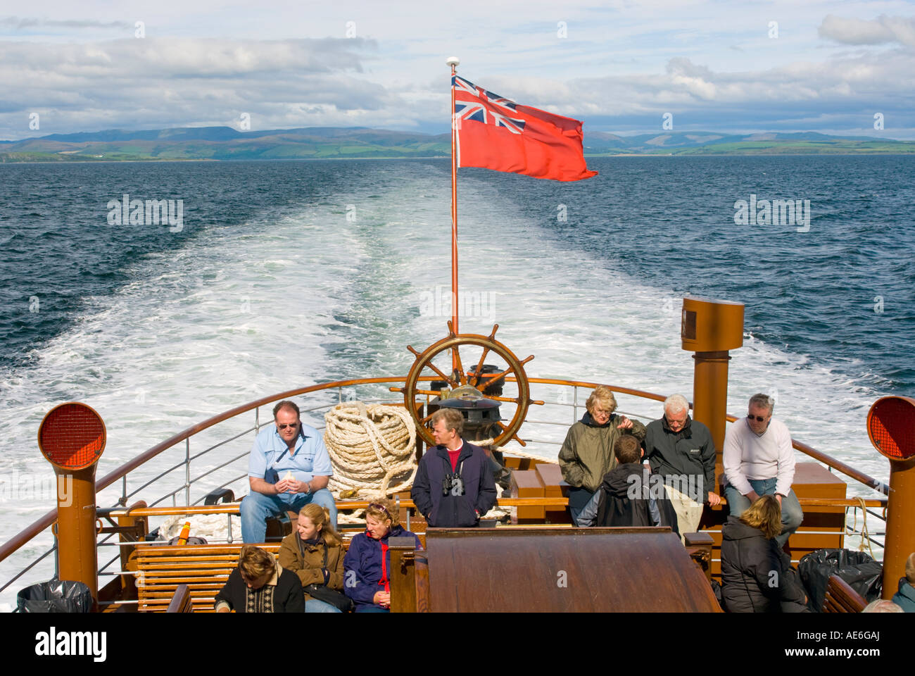Passengers enjoy the sun on the aft deck of Paddle Steamer Waverley as she cruises on the Firth of Clyde, Scotland. Stock Photo