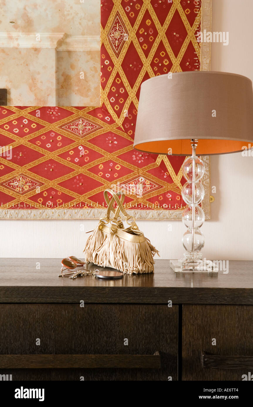 Stylish lamp and bag on sideboard beneath decorated mirror - Stock Image