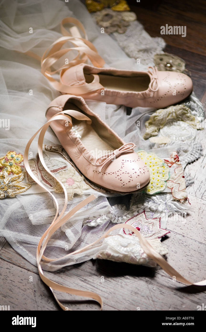 Child's ballet dance shoes on piece of embroidered lace - Stock Image