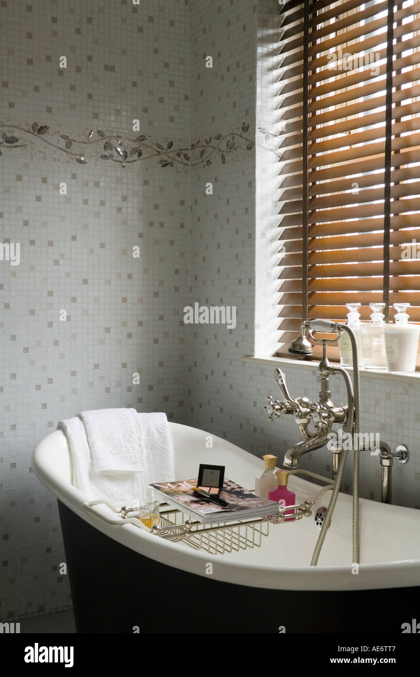 Victorian freestanding bath in bathroom with mosaic wall - Stock Image