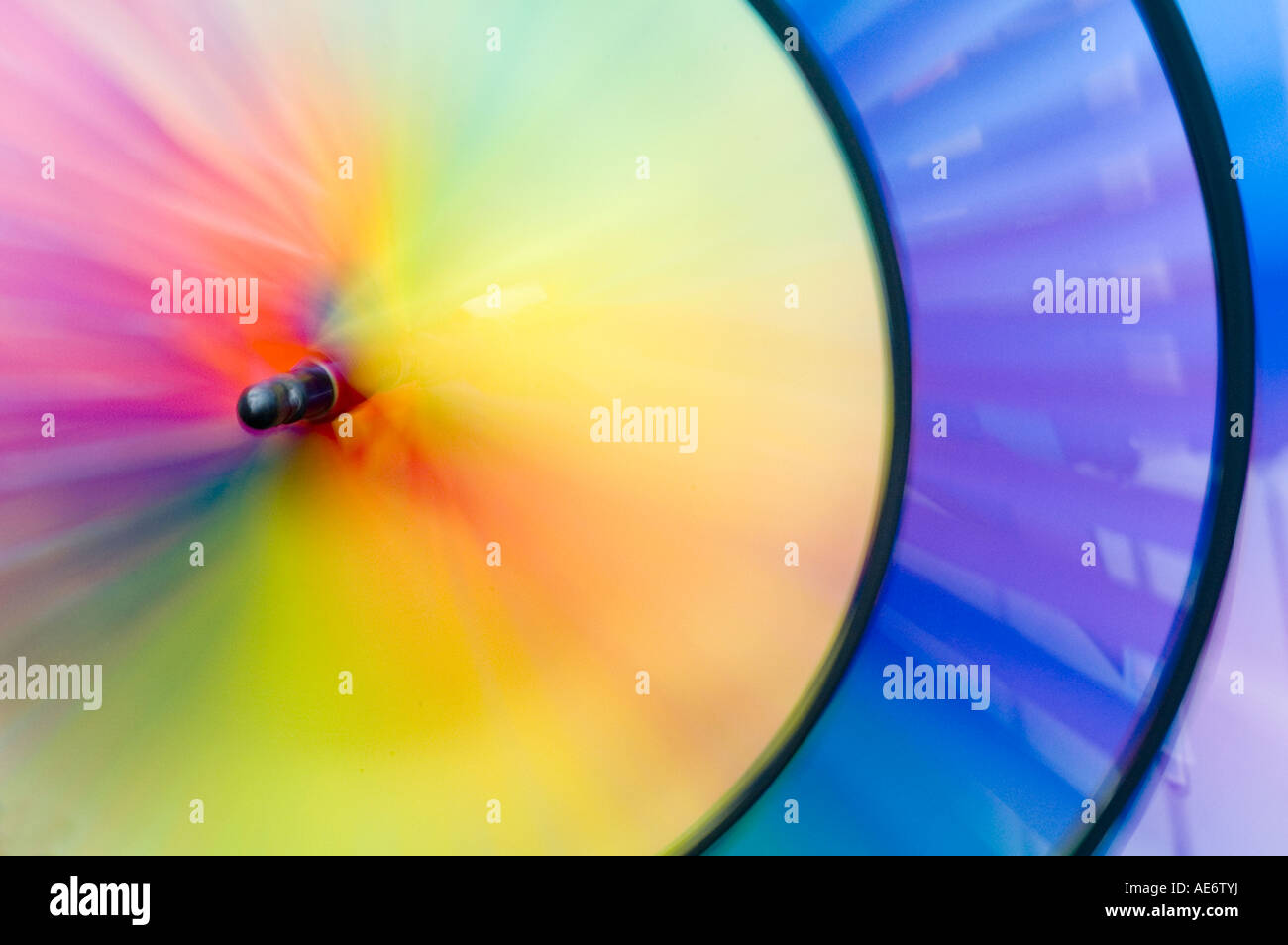 Windmill III. A spiral weather vane or wind vane made of colorful strips of cloth and sprockets - Stock Image