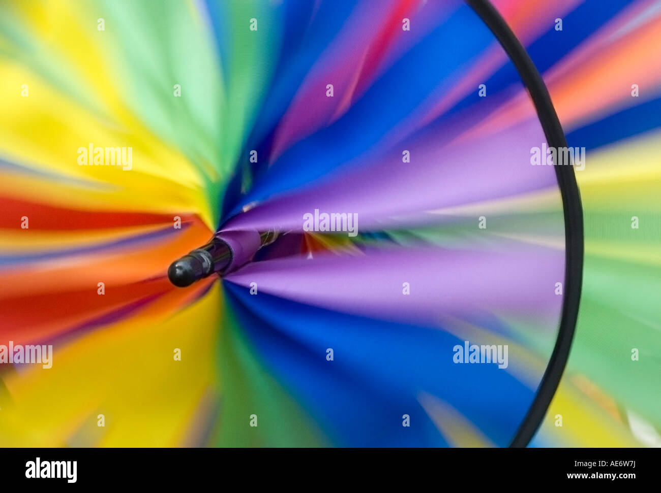 A decorative windmill. A spiral weather vane or wind vane made of colorful strips of cloth and sprockets - Stock Image