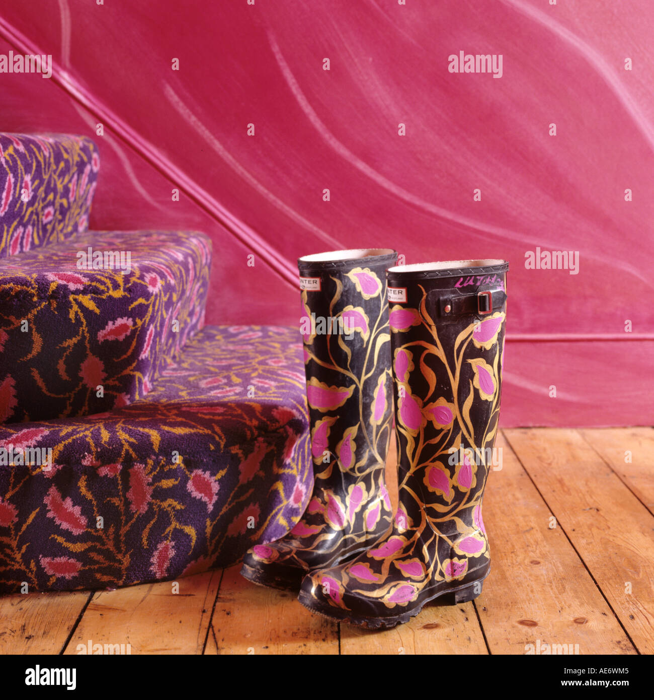 Hand-painted wellington boots by matching carpeted stairs - Stock Image