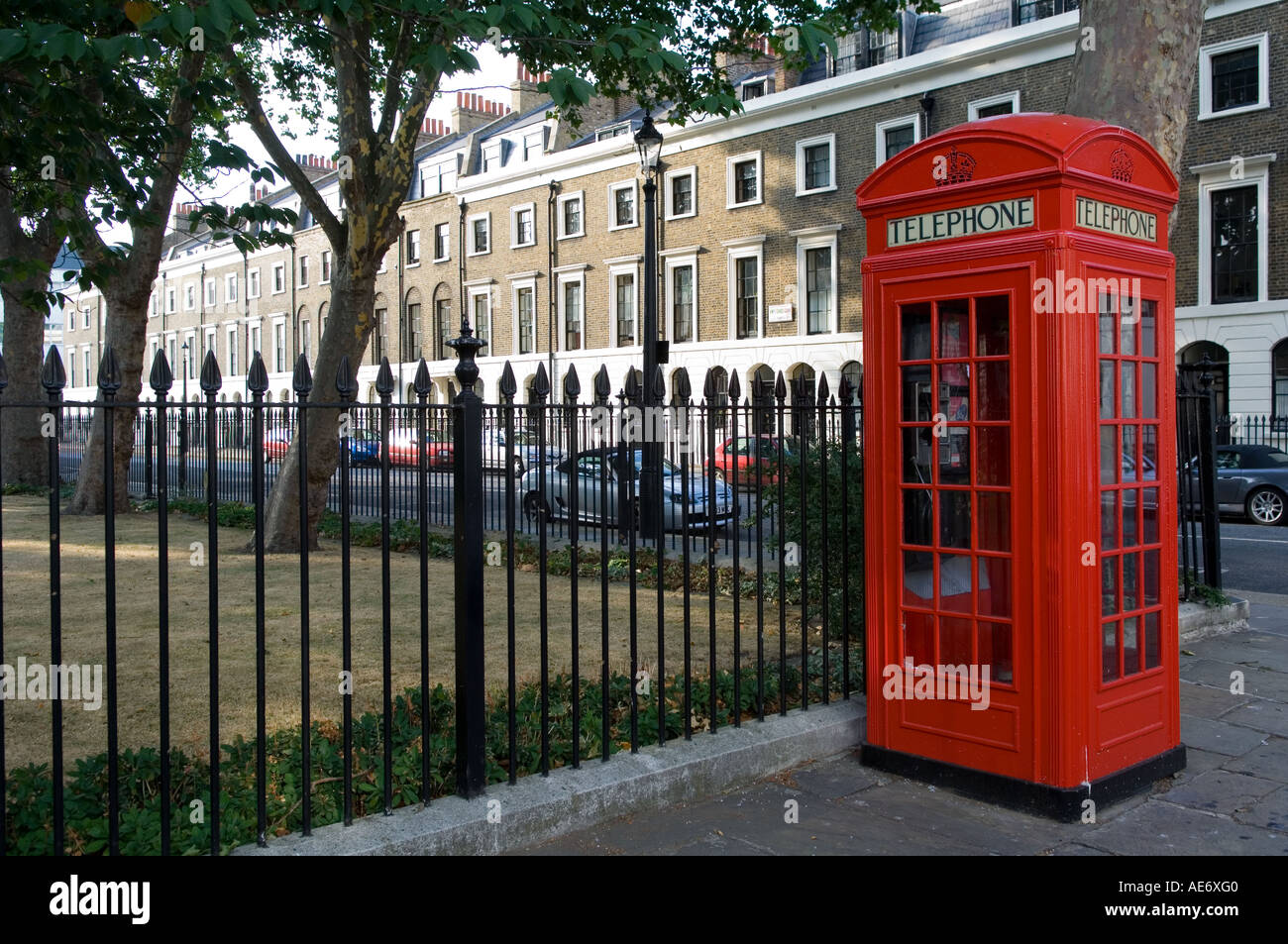 London garden square with red telephone kiosk and black iron railings - Stock Image