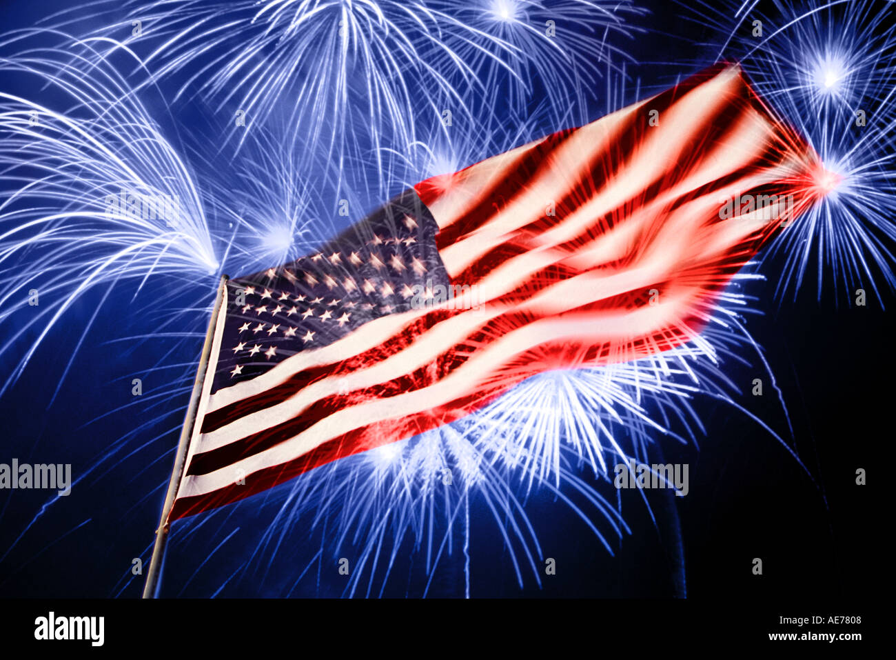 american flag at night with fireworks exploding in the air above