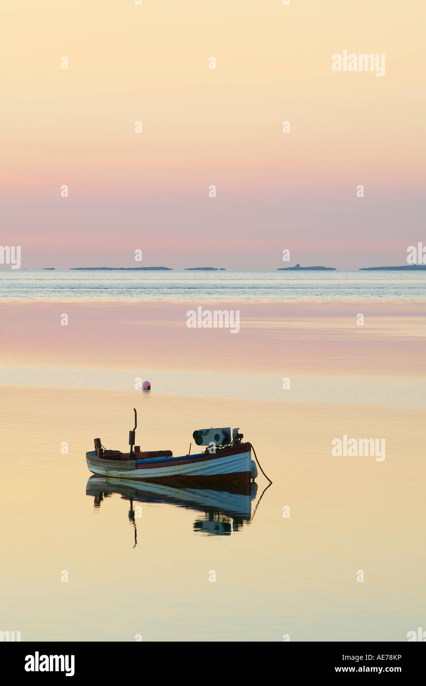 Small boat at dawn Holy Island Northumberland England The Farne Islands are on the horizon Stock Photo