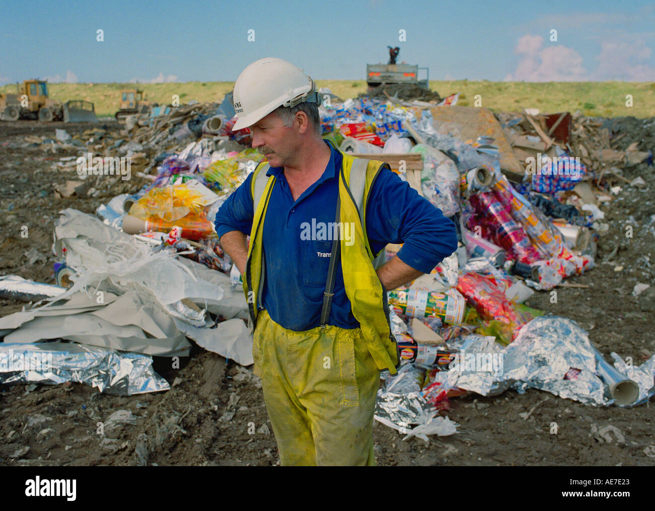 Lorry driver dumping unused Walkers crisp packaging at an industrial landfill site in West Cumbria UK - Stock Image