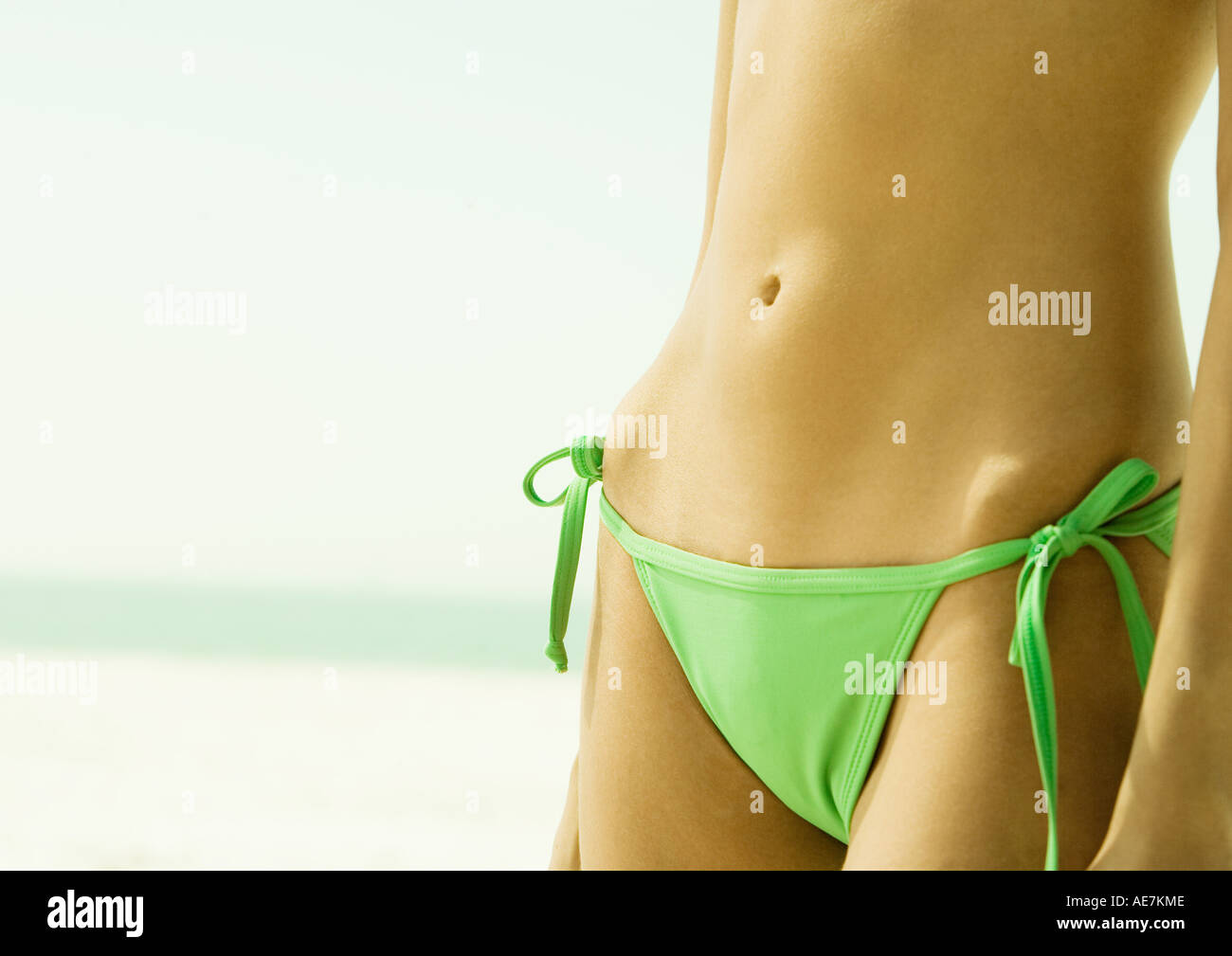 Woman wearing string bikini, close-up of abdomen - Stock Image