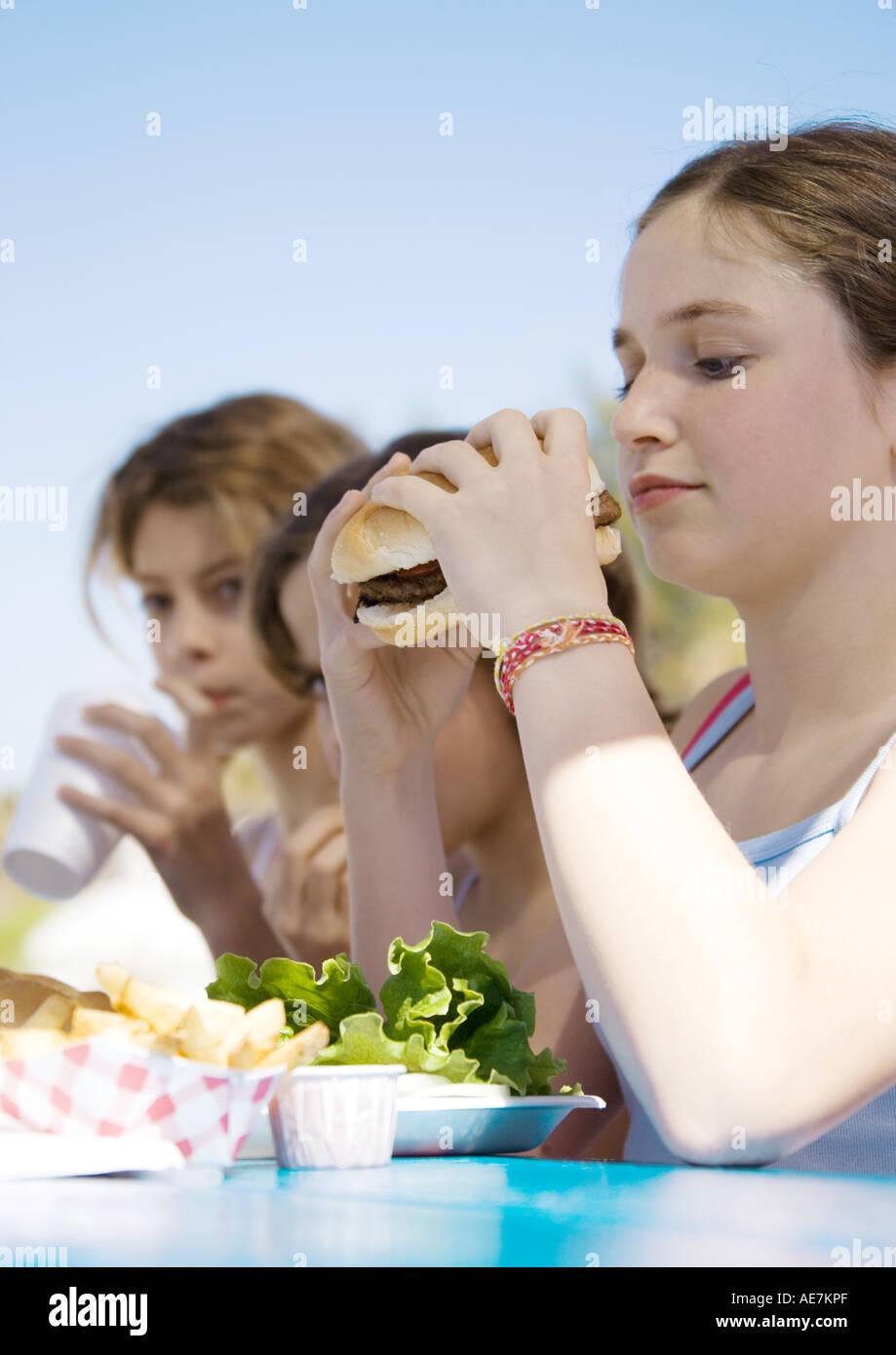Kids eating hamburgers - Stock Image