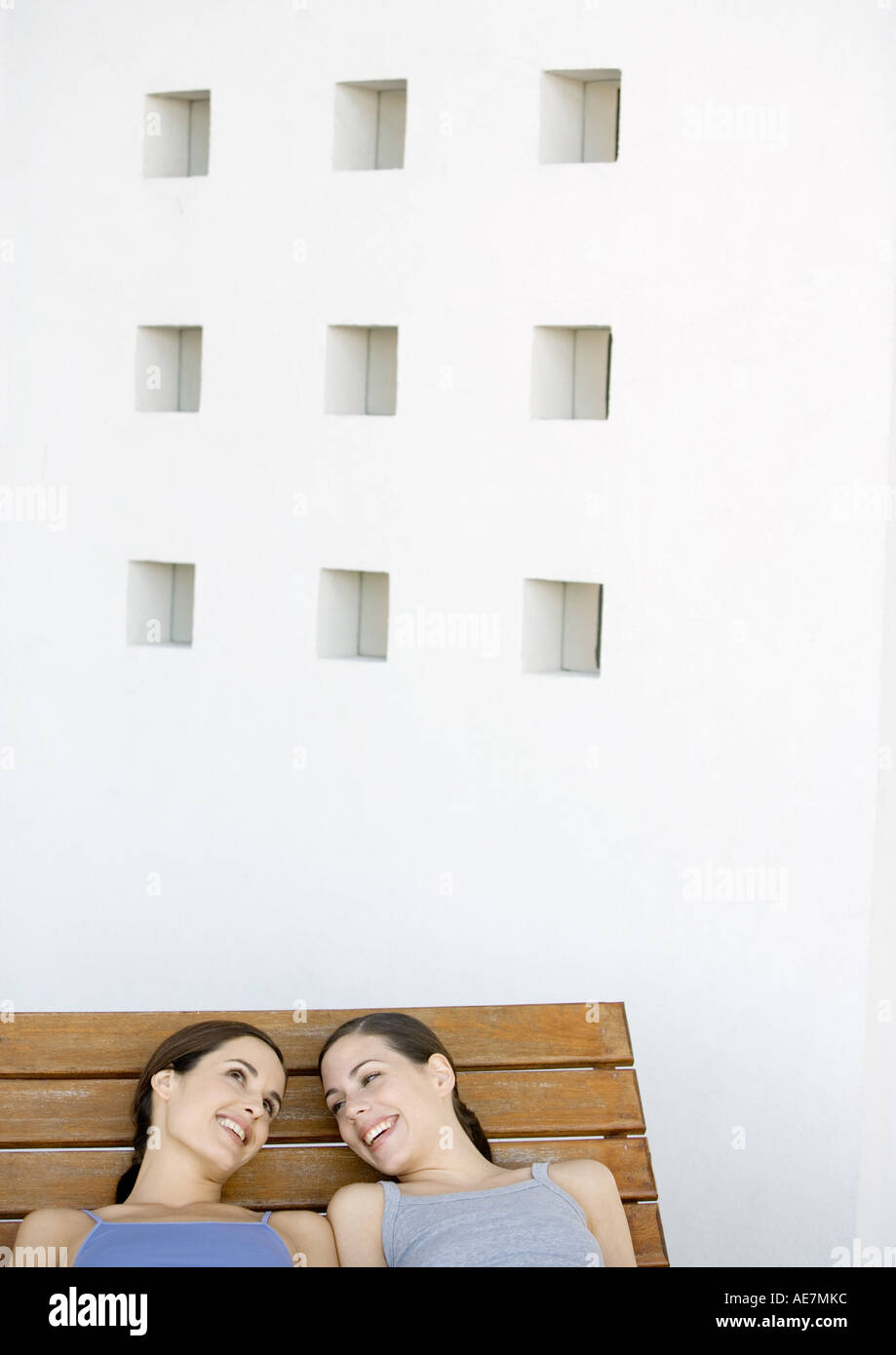 Two young women reclining and talking side by side - Stock Image