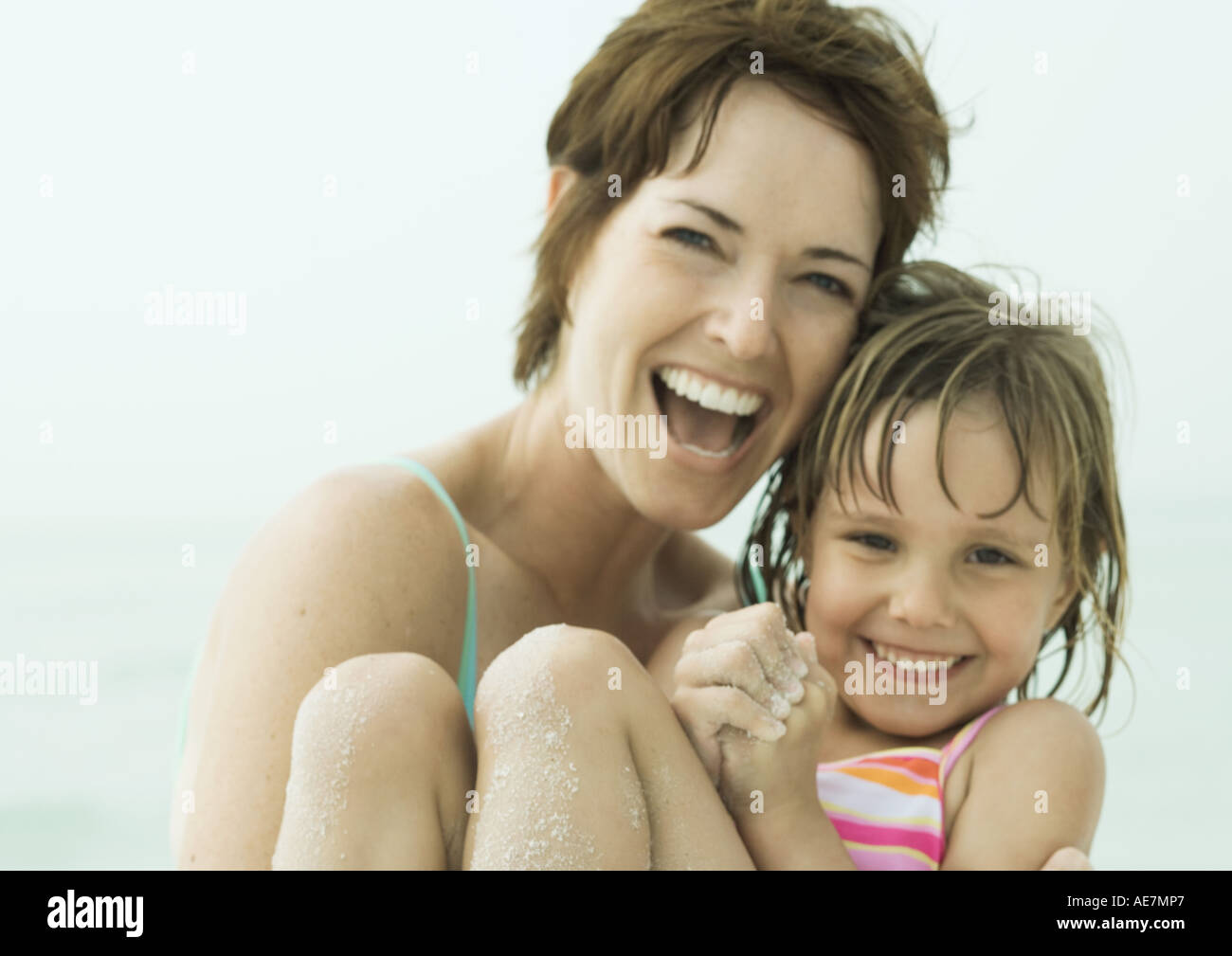 Mother holding daughter at the beach, close-up - Stock Image