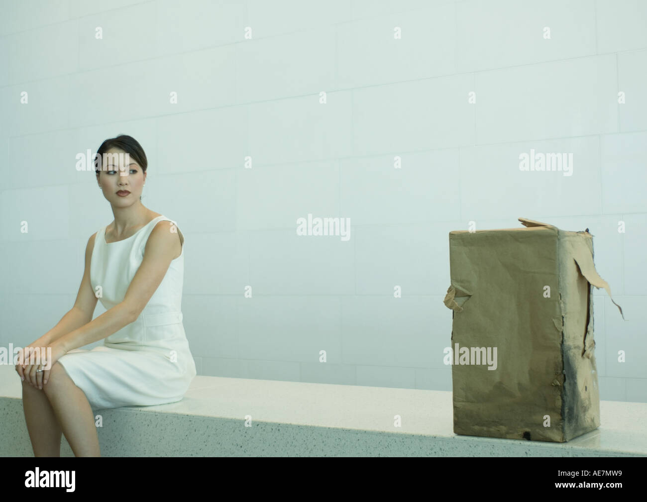 Woman sitting on bench looking at suspicious package - Stock Image