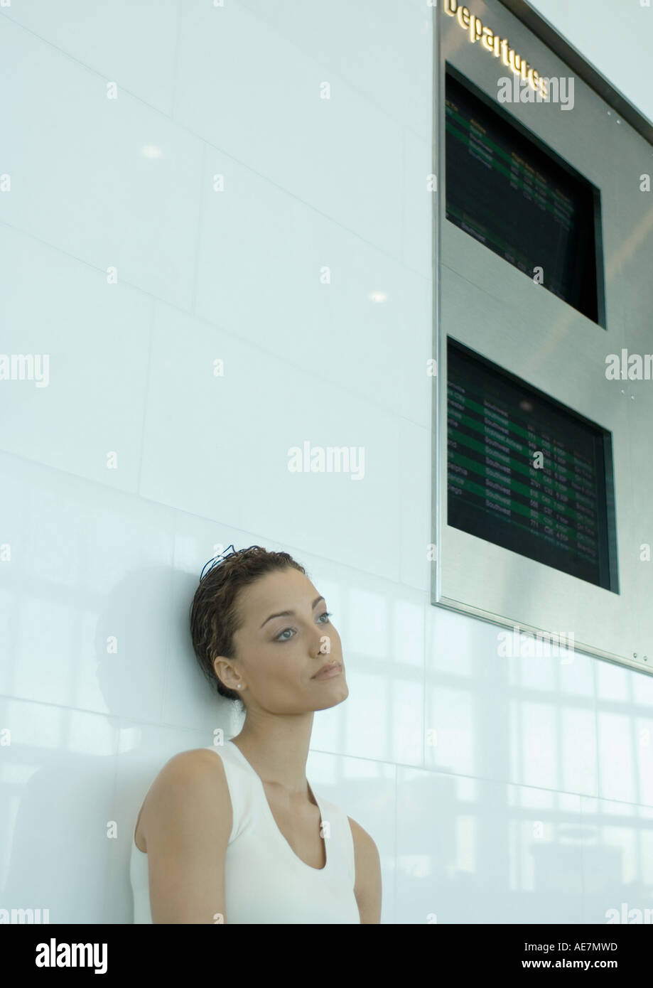 Woman leaning against wall below arrival and departure boards - Stock Image