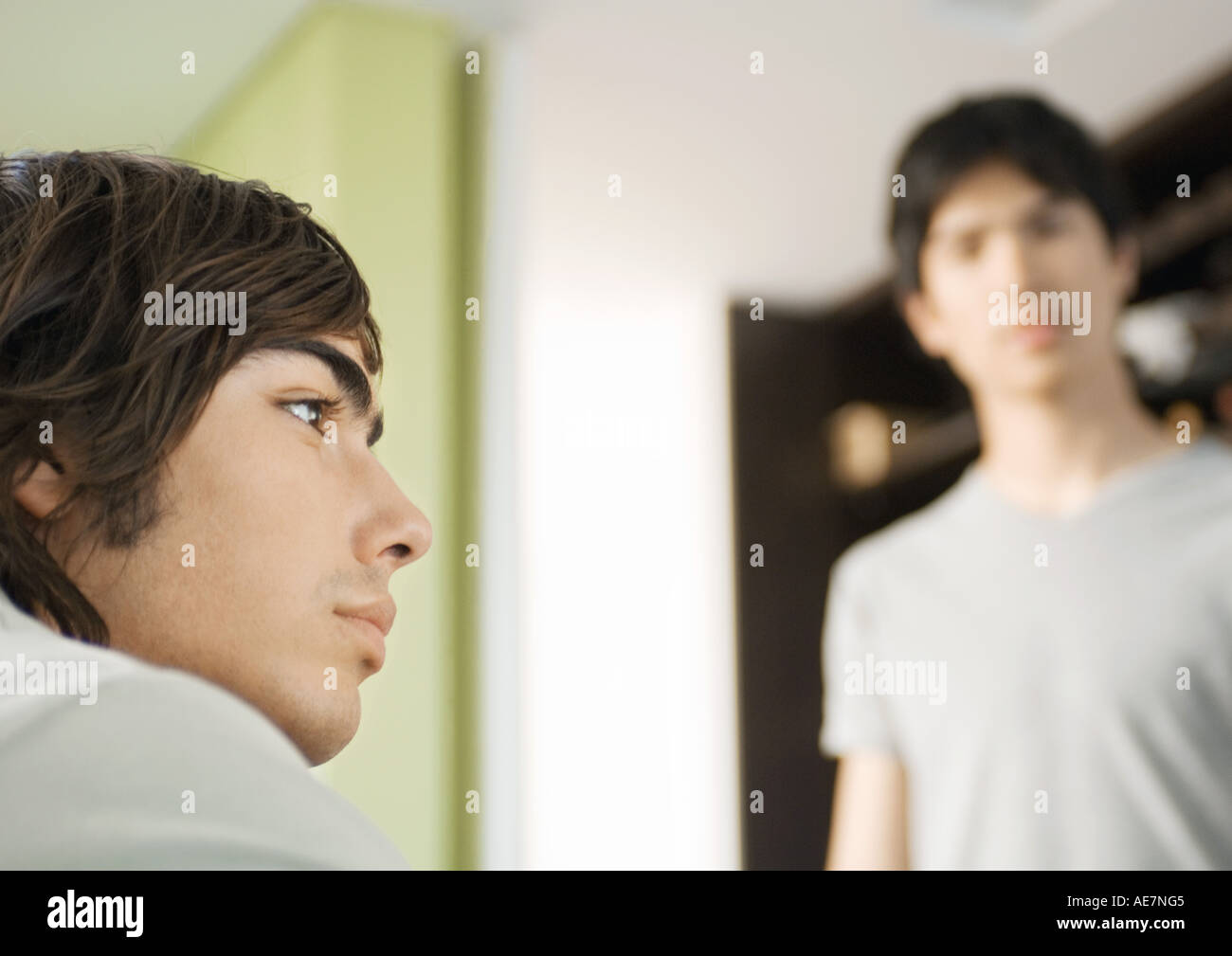 Young man looking away, friend in background - Stock Image