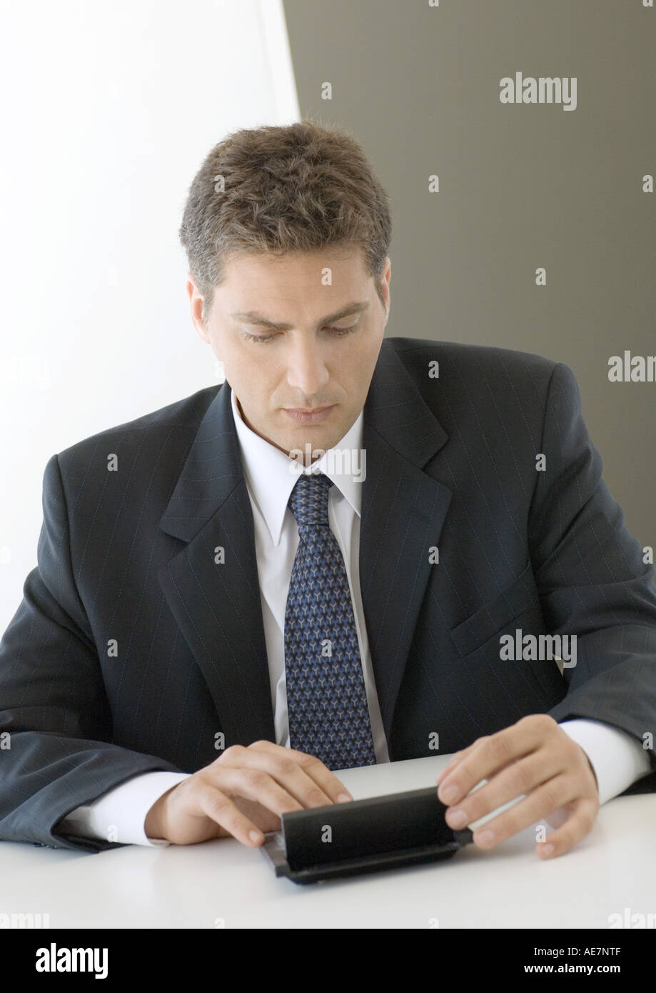 Businessman using pocket computer - Stock Image
