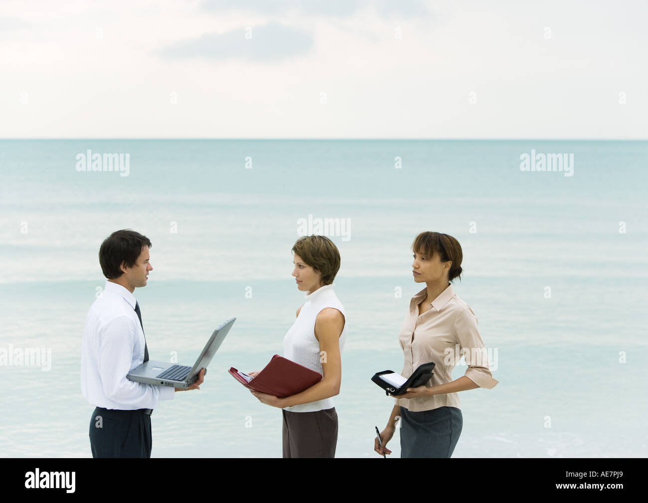 Businessman holding laptop, facing women holding agendas, sea in background Stock Photo