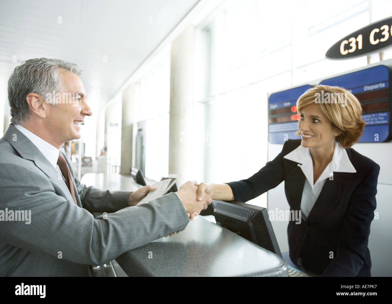 Airline attendant shaking hands with passenger at check-in counter - Stock Image