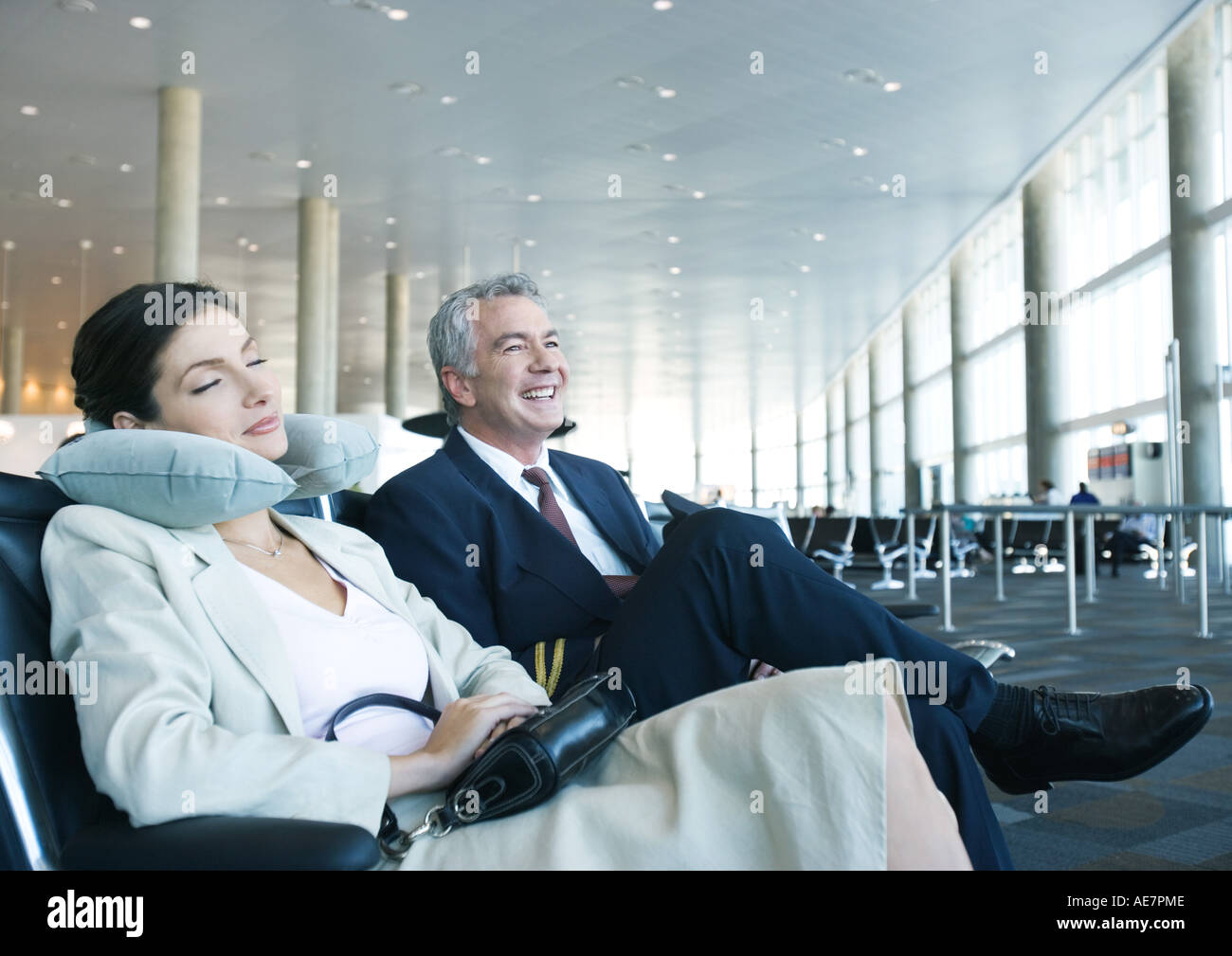 Business travelers sitting in airport lounge, woman napping with neck pillow next to smiling man Stock Photo