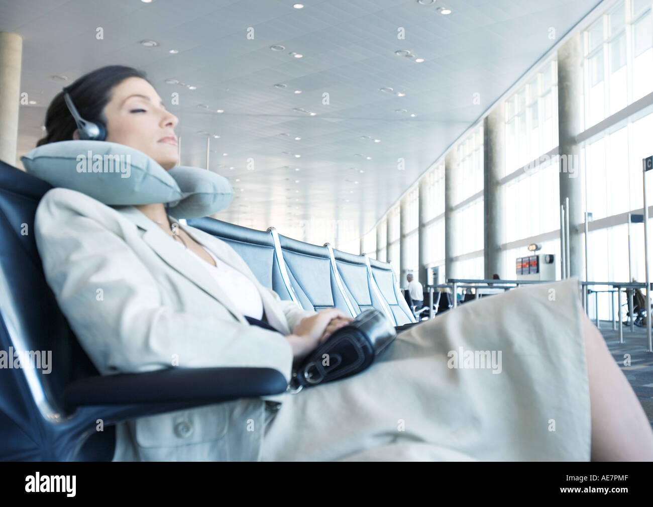 Business traveler sitting in airport lounge, napping with neck pillow - Stock Image