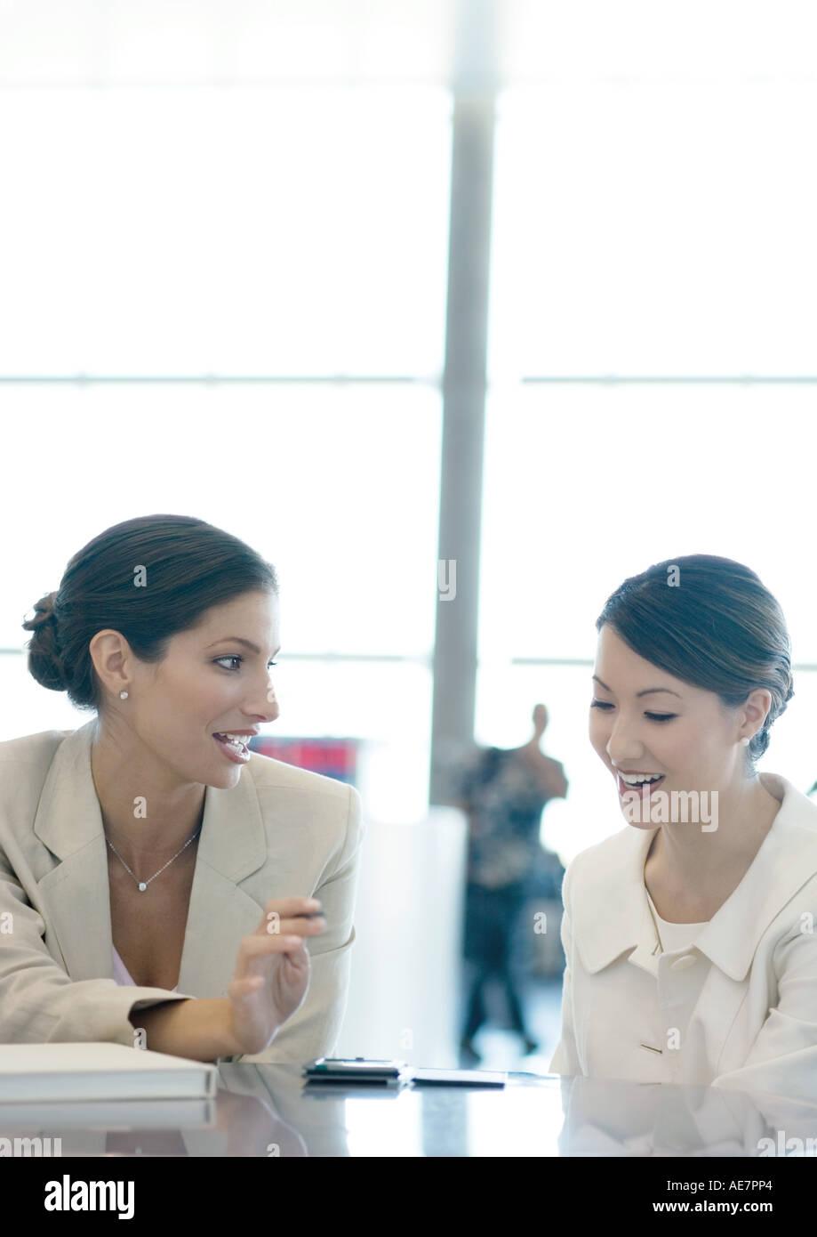 Businesswomen talking, one looking at electronic organizer - Stock Image