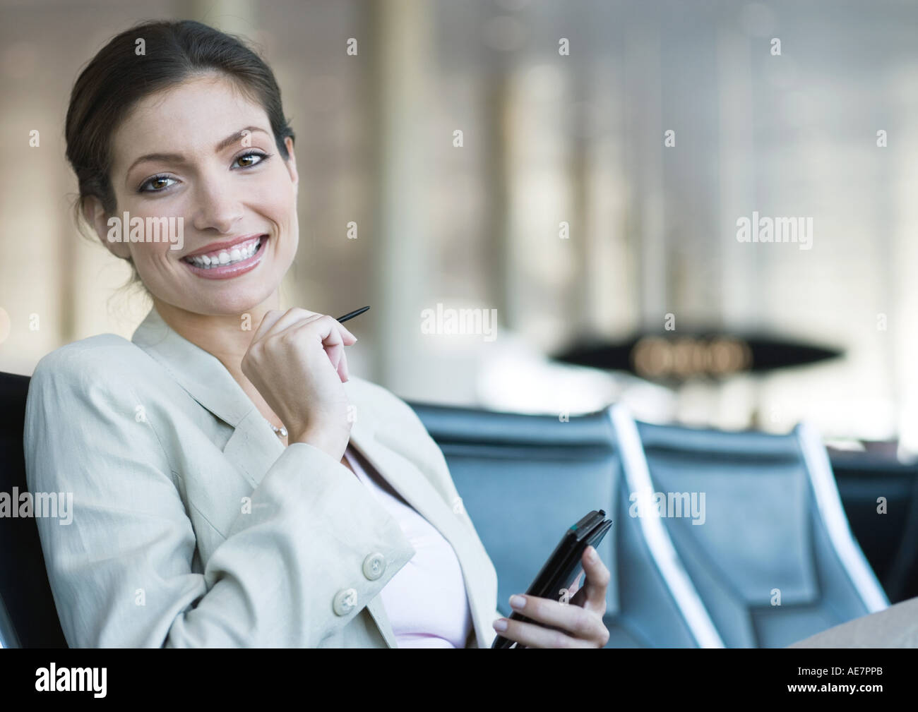 Businesswoman using electronic organizer in airport lounge area, smiling at camera - Stock Image