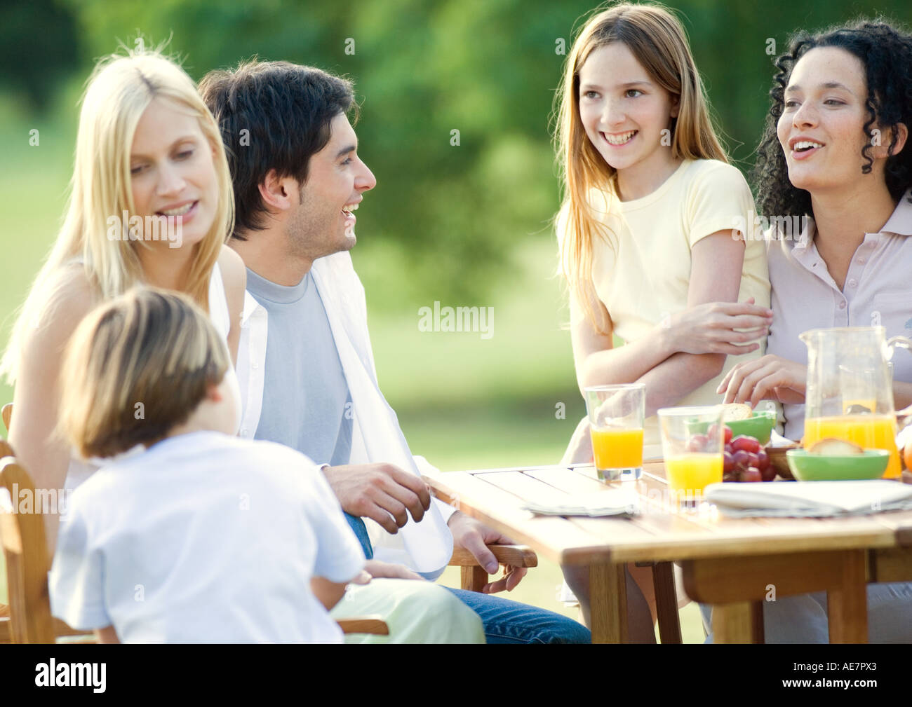Family and kids sitting around table outdoors - Stock Image