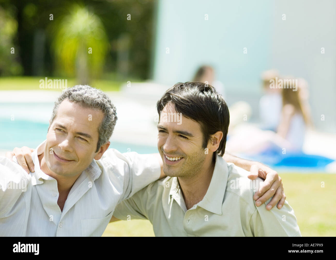 Two men with arms around each other's shoulders, smiling Stock Photo