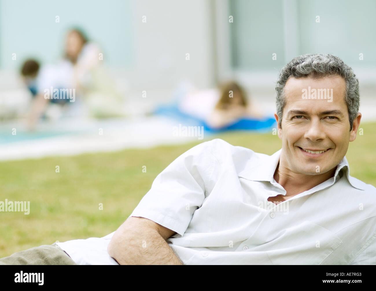 Man relaxing in yard - Stock Image