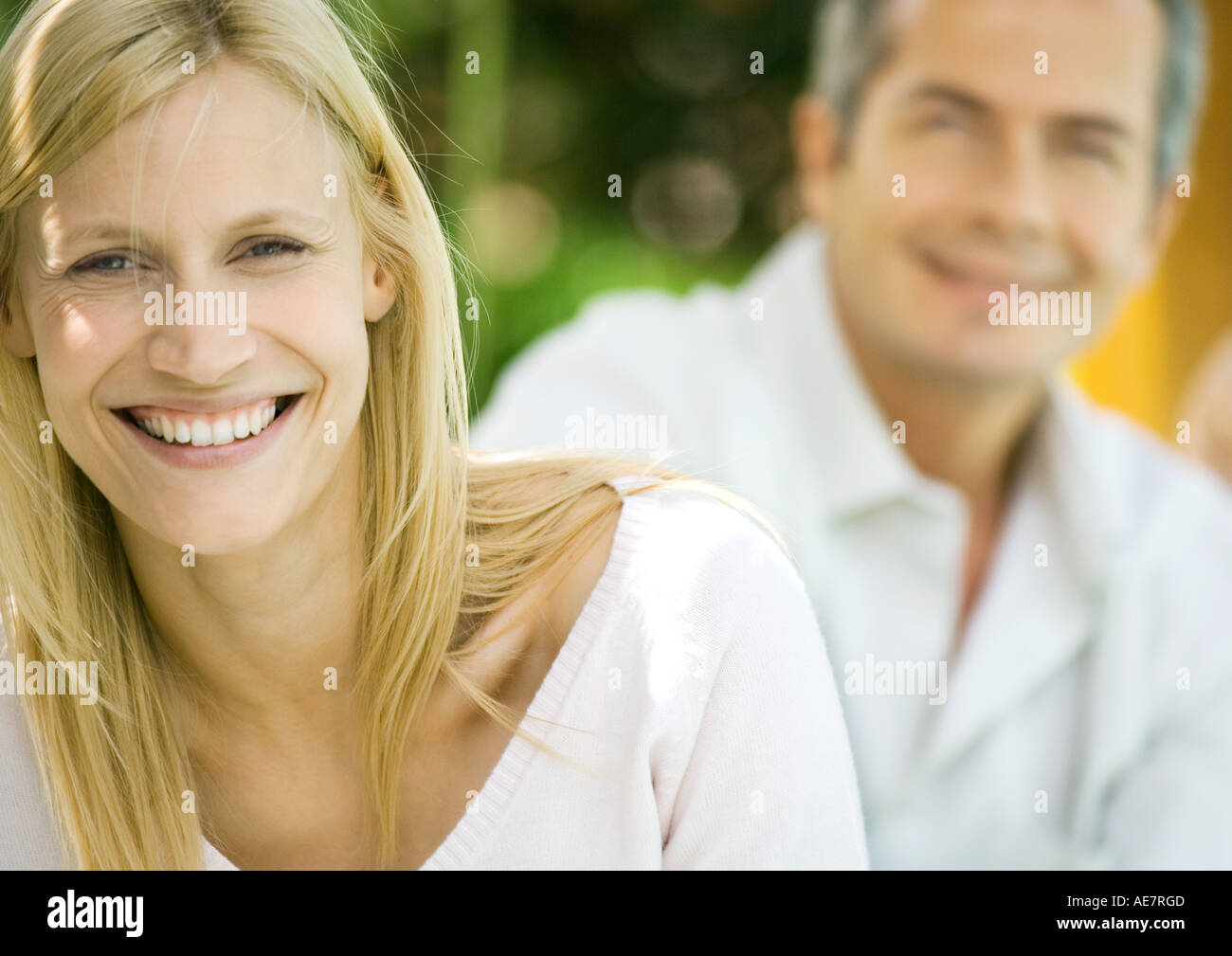 Woman smiling, man in background, portrait - Stock Image