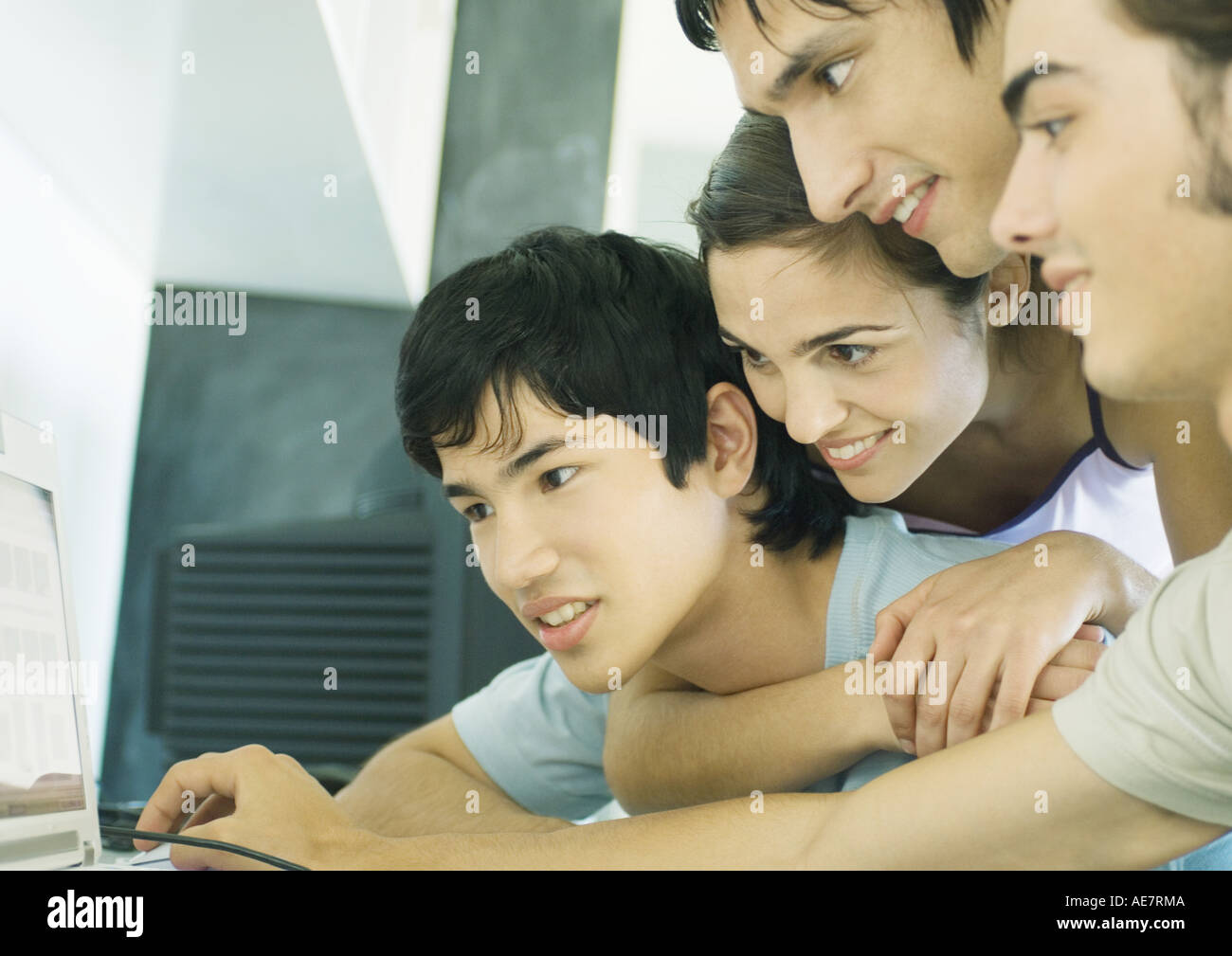 Four young adult friends looking at computer screen together Stock Photo