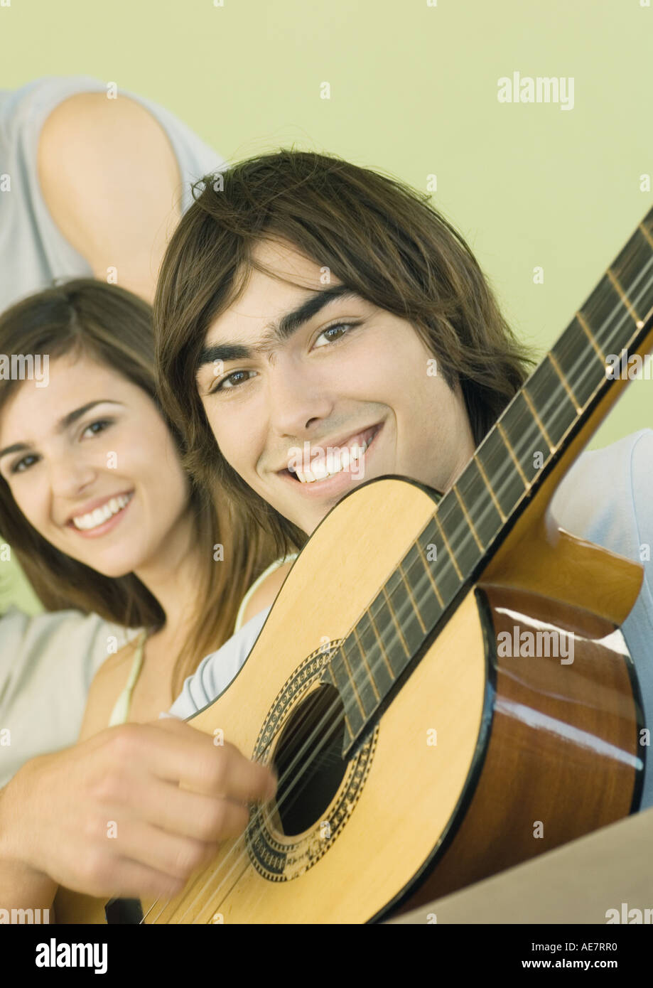 Young man playing guitar for friends - Stock Image