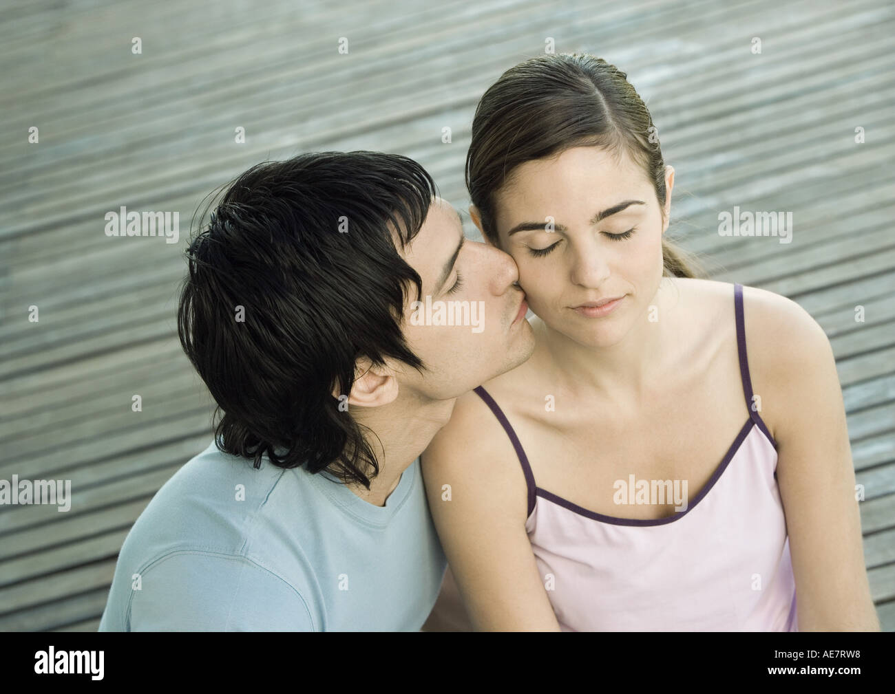 Young man kissing his girlfriend on the cheek, closed eyes, portrait - Stock Image