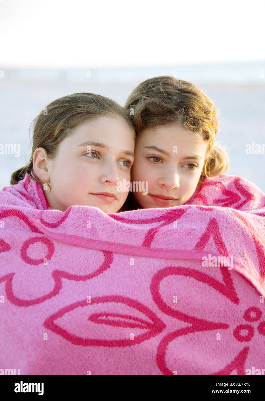 Two girls wrapped in towel together - Stock Image