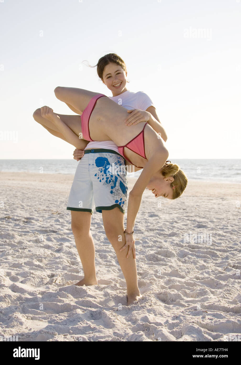 Girl flipping sister over on beach - Stock Image