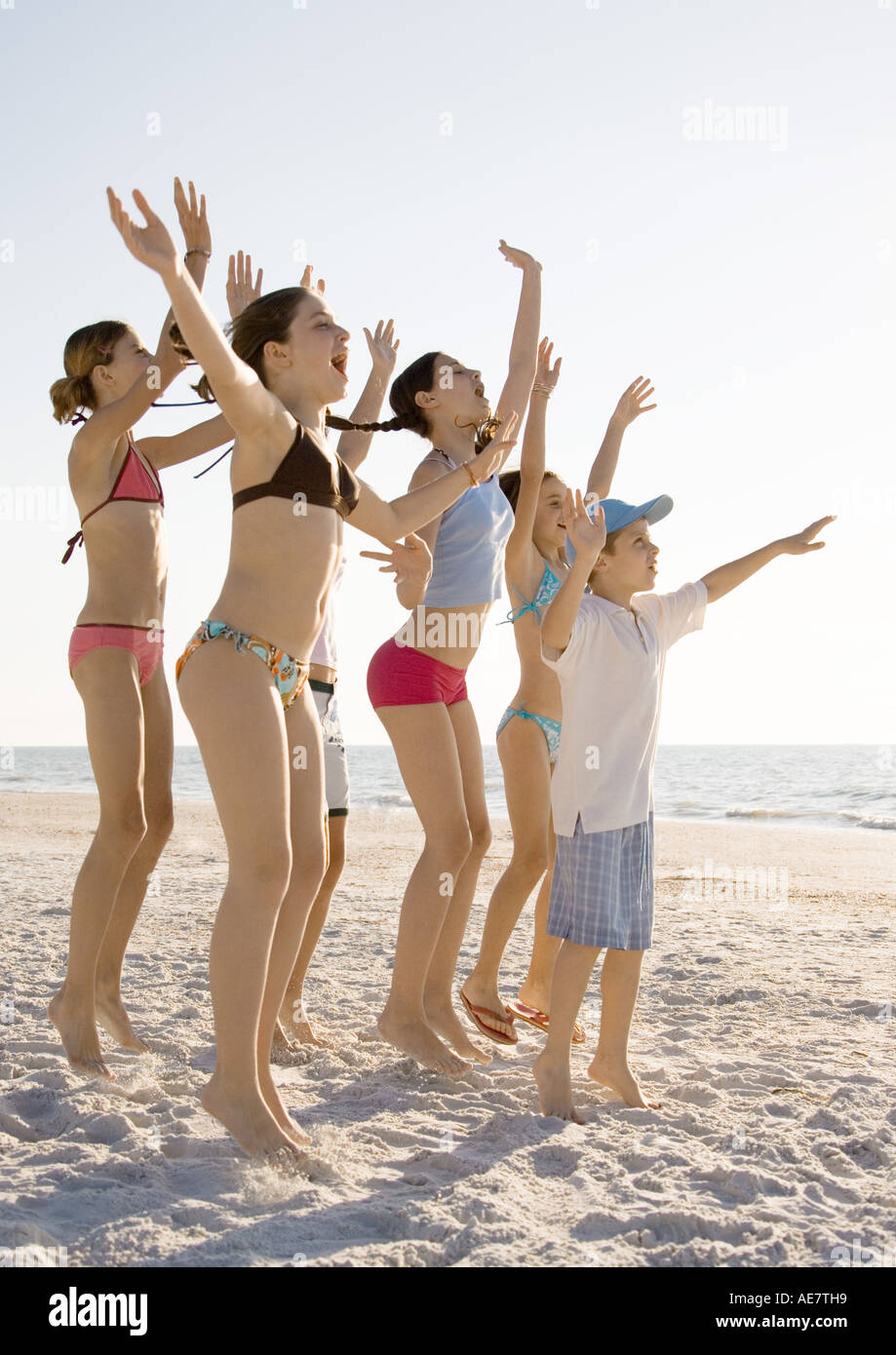 Group of kids jumping and waving on beach - Stock Image