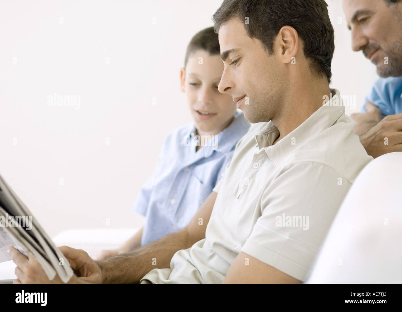 Man looking at newspaper with son and father - Stock Image