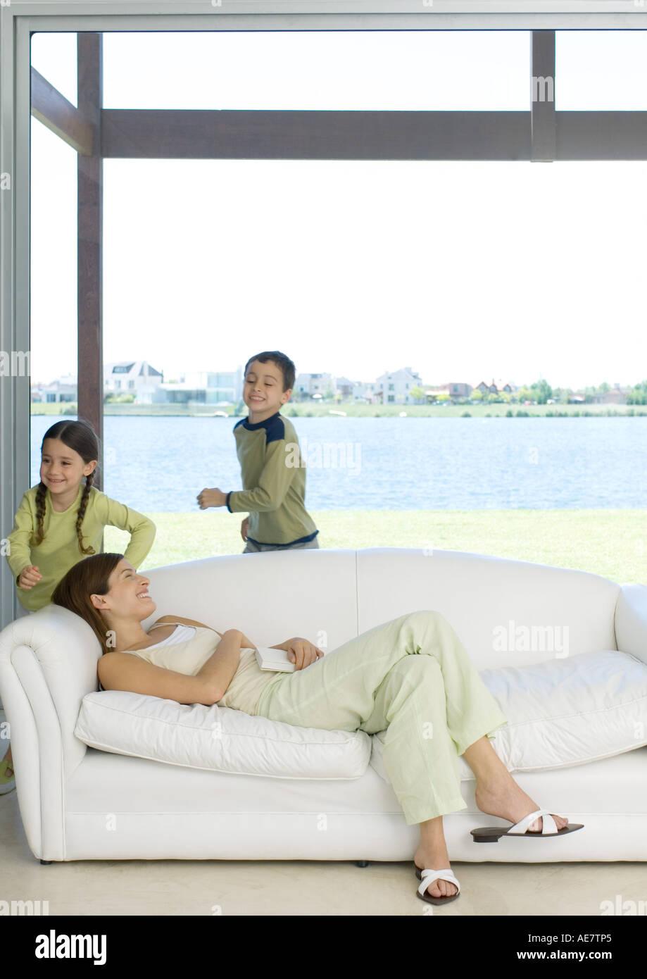 Mother reclining on sofa while children run around her Stock Photo