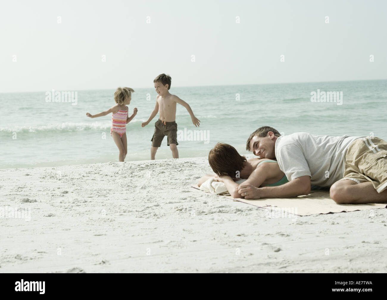 Parents lying on beach while children play in background - Stock Image