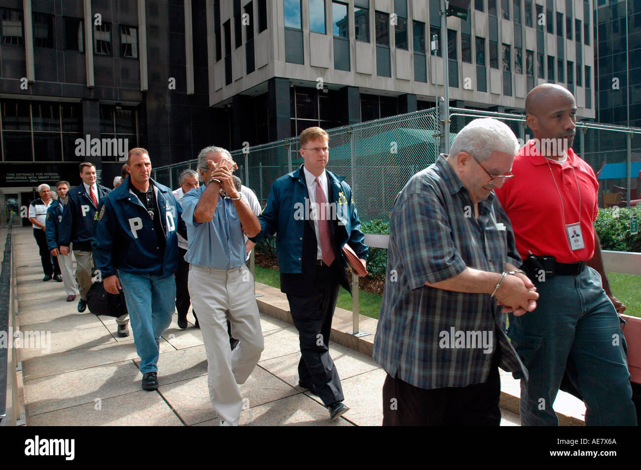 NYC Police Detectives and FBI agents escort some elderly and middle aged alleged mobsters out of the booking facility  - Stock Image